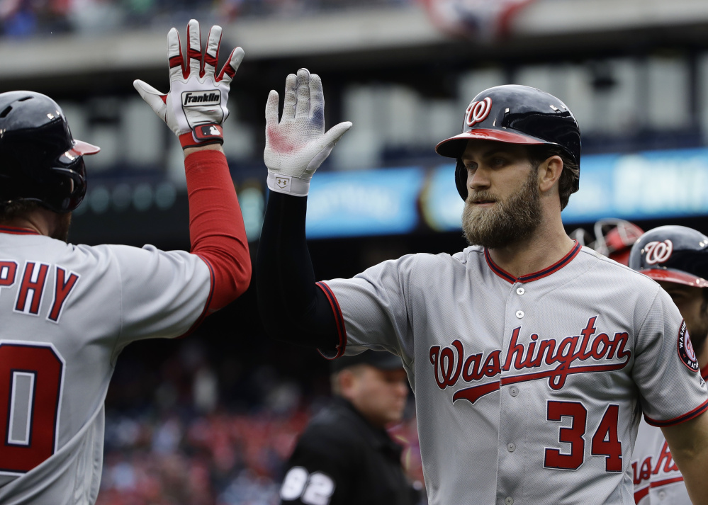 Washington's Bryce Harper, right, celebrates with Daniel Murphy after hitting a two-run homer in the first inning of a 7-6 win against the Phillies on Friday at Philadelphia.