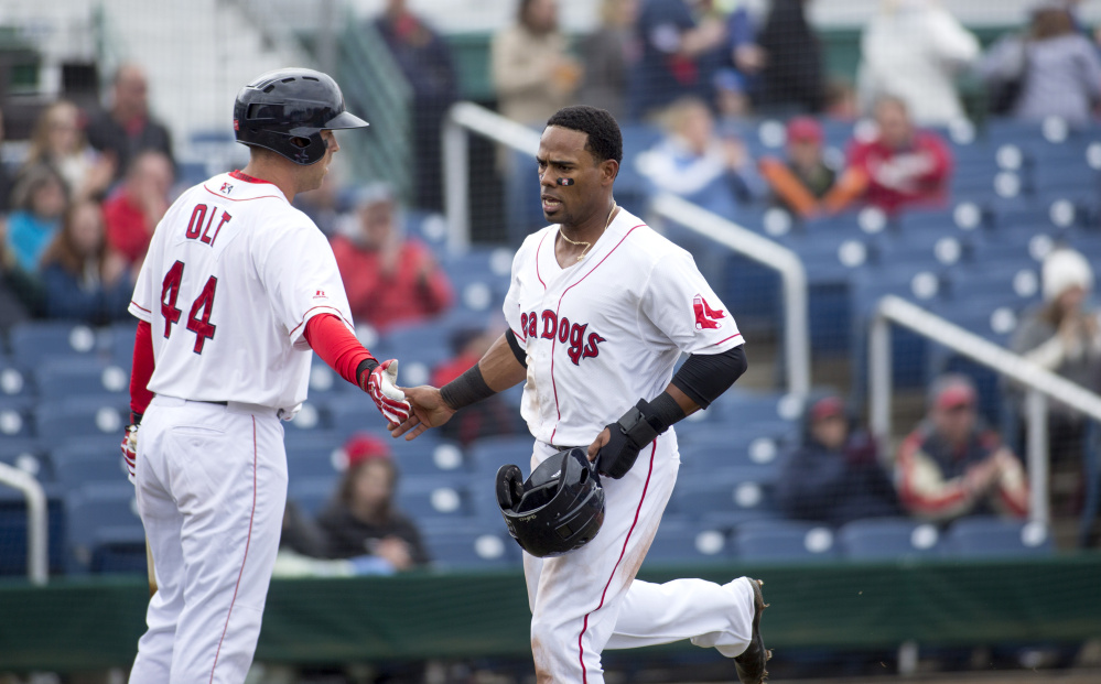 PORTLAND, ME - APRIL 8: Sea Dog's Aneury Tavarez (20) high fives his teammate Mike Olt (44) as he runs into home during the game against the Reading Fighting Phils. The Sea Dogs won (4-1). (Staff photo by Brianna Soukup/Staff Photographer)