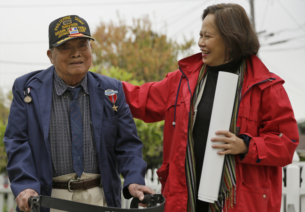 Bataan Death March survivor Ramon Regalado walks with Cecilia Gaerlan outside his home in El Cerrito, Calif. Survivors marked the 75th anniversary of the march on Saturday in San Francisco.