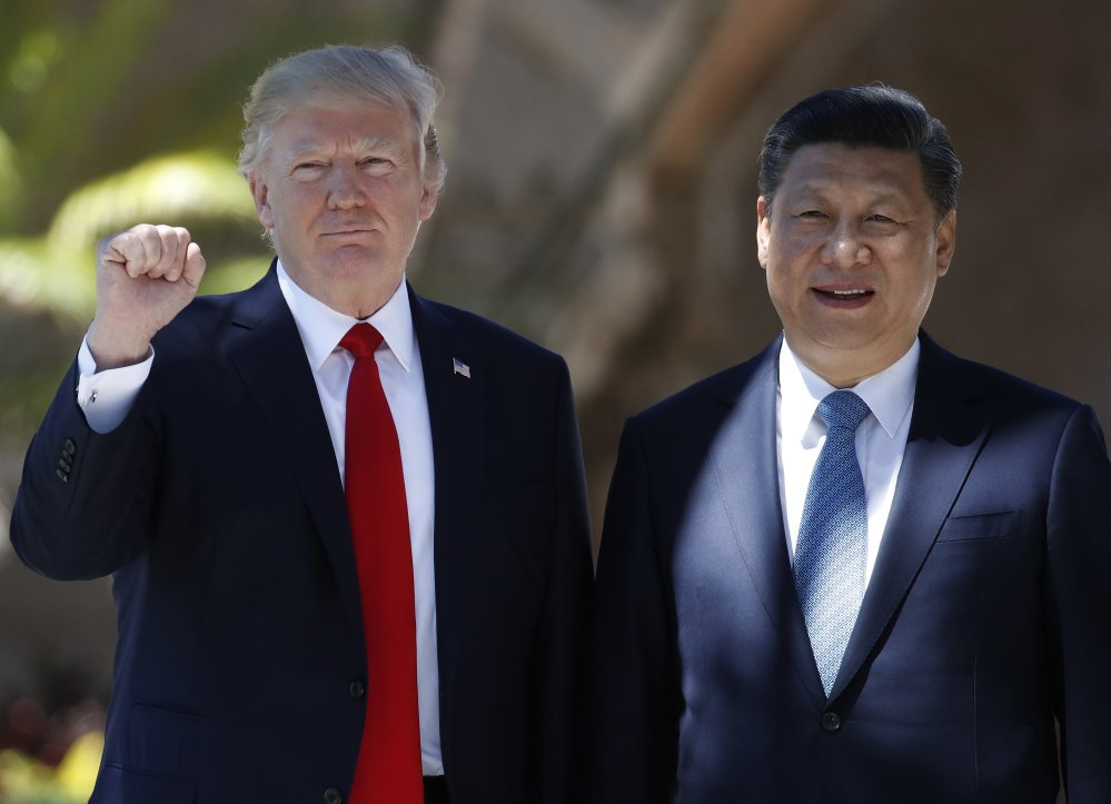 President Donald Trump and Chinese President Xi Jinping pause for photographs at Mar-a-Lago in Palm Beach, Fla., on Friday.