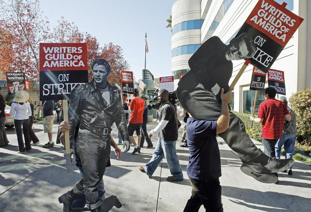 In 2007, striking writers carry life-sized photos of legendary actors, Marlon Brando, left, and James Dean to express their support to members of the Writers Guild of America. While television enjoys a Golden Age, the WGA claims the writers aren't being paid like it.