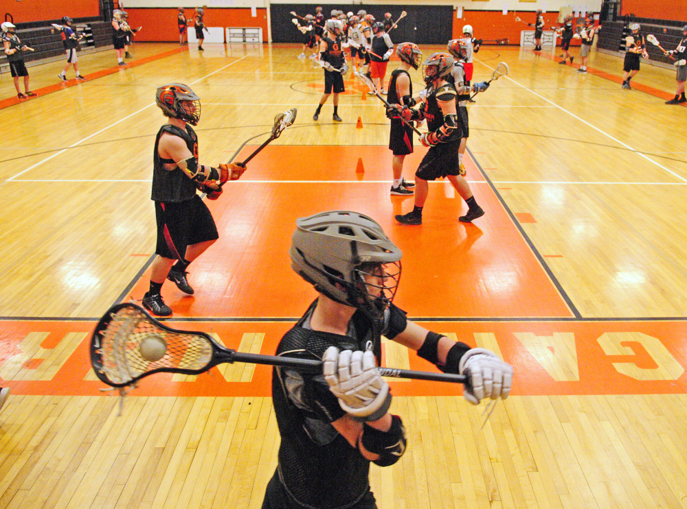 The Gardiner boys lacrosse team runs through drills during practice Tuesday at Gardiner Area High School.