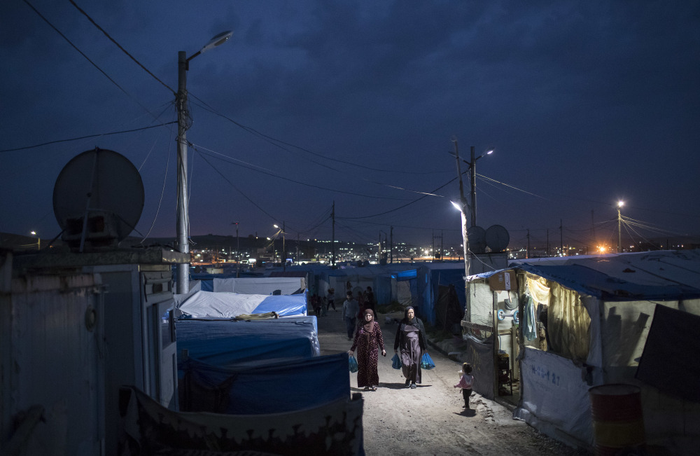 Syrian women walk at dusk in a refugee camp in northern Iraq on Saturday. For millions of refugees, the chemical attack in Syria followed by the U.S. strike was a rare moment when the world briefly turned its attention to Syria, before turning away again.