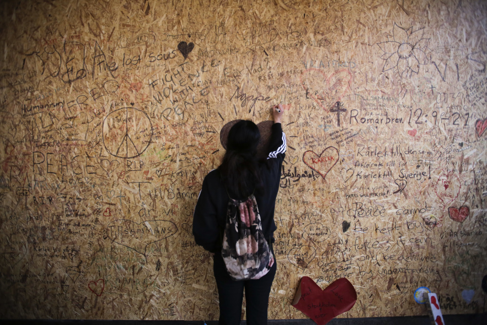 A woman writes a message on a wooden board Sunday at the Ahlens department store in Stockholm, Sweden, where the hijacked truck crashed Friday. Four people died in the rampage and 10 of the 15 people injured remained hospitalized Sunday, including one child.