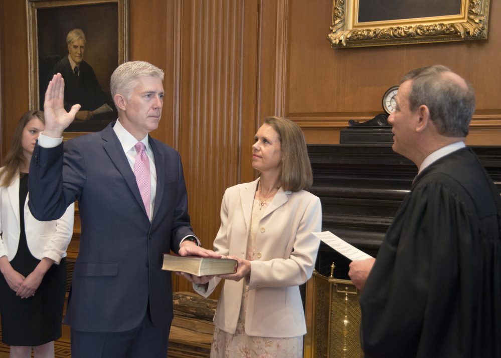 U.S. Chief Justice John G. Roberts Jr. administers the Constitutional Oath to the Neil Gorsuch in a private ceremony attended by the justices of the Supreme Court and members of the Gorsuch family, including his wife, Louise Gorsuch, on Monday in Washington.