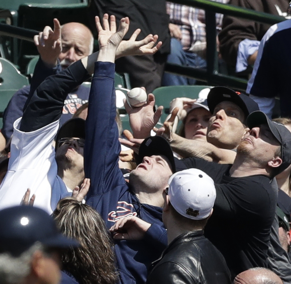 Baseball fans at Detroit's Comerica Park present an array of hands and facial expressions as they reach for a foul ball off the bat of Minnesota's Jorge Polanco during a 5-3 comeback win by the Tigers on Wednesday afternoon.
