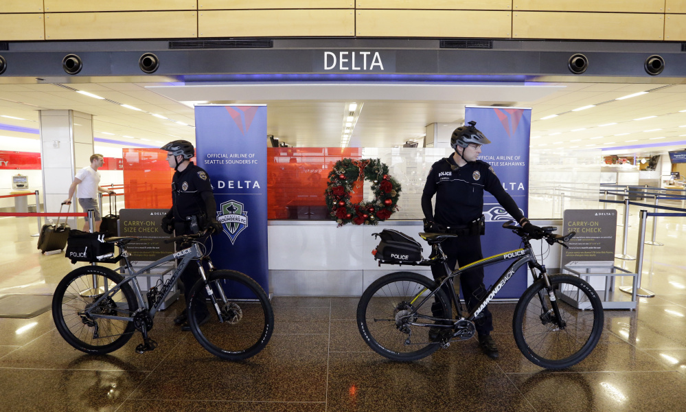 Police officers stand ready at Seattle-Tacoma International Airport last year. A police research group says airlines should think carefully before asking police to intervene.