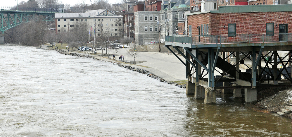 People stand around a puddle in the lowest part of the parking lot as the Kennebec River starts to crest over the banks.