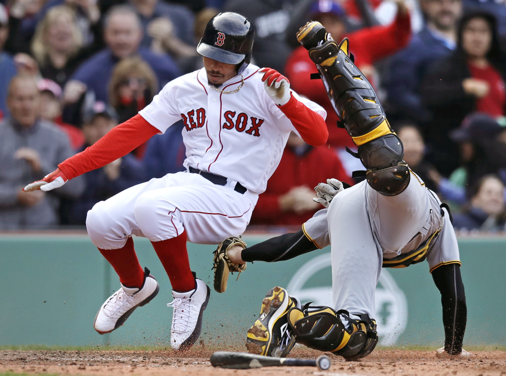 Pittsburgh catcher Chris Stewart, right, tags out Boston's Mookie Betts, who wase trying to score on a hit by Hanley Ramirez during the eighth inning of Thursday's game at Fenway Park in Boston.