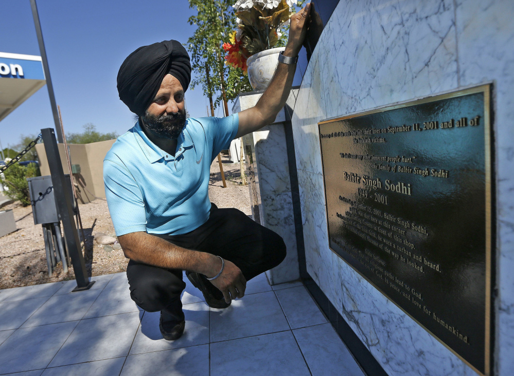 Rana Singh Sodhi kneels near his service station last summer in Mesa, Ariz., next to a memorial for his brother, Balbir Singh Sodhi, who was murdered in the days after the Sept. 11 terrorist attacks by a man who said he wanted to kill Muslims.