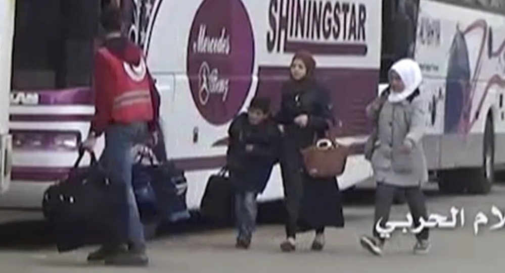 Video provided by the Syrian Central Military Media shows a Syrian Red Arab Crescent volunteer carrying bags of a family heading to a bus as they leave the town of Madaya.