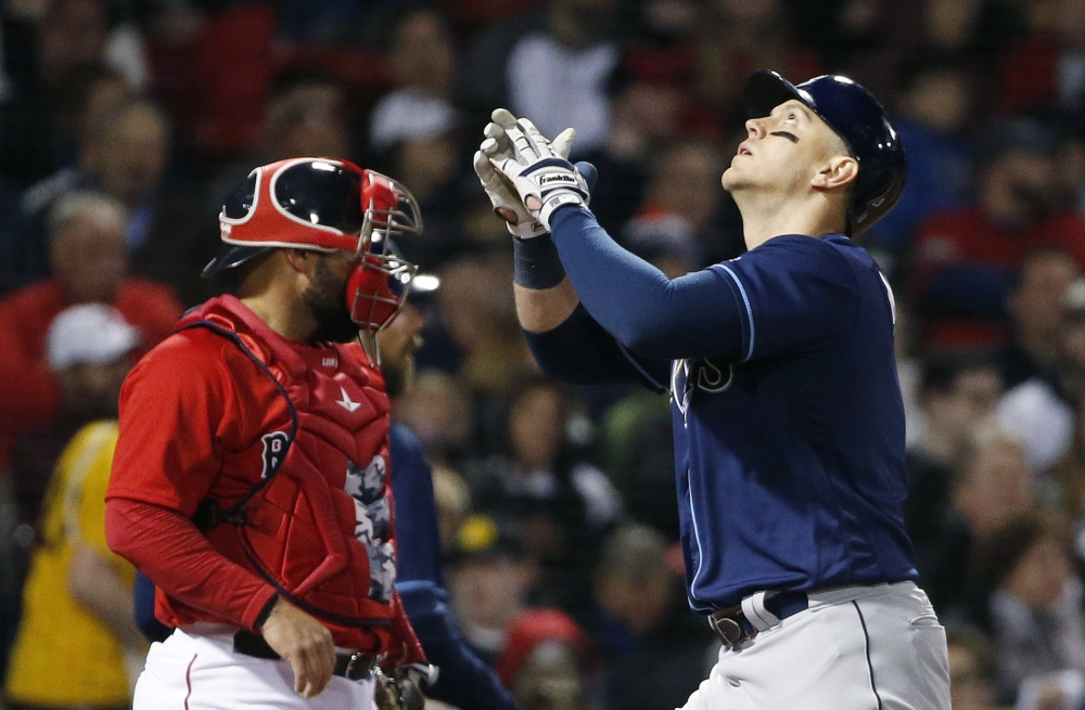Logan Morrison of the Tampa Bay Rays celebrates after hitting a grand slam Friday night in front of catcher Sandy Leon of the Boston Red Sox during the third inning of the Rays' 10-5 victory at Fenway Park.