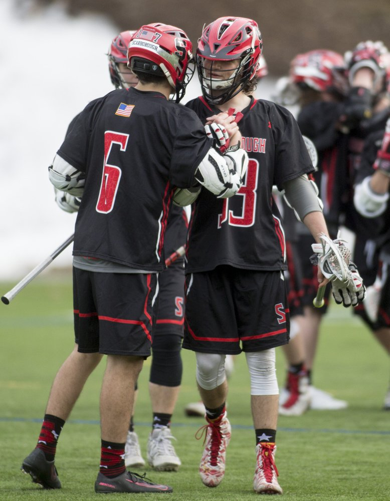 Marco Manfra, left, celebrates with Drew Cusson after one of his three goals for Scarborough. The Red Storm began defense of their Class A state championship by defeating a Gorham team that reached the regional final last year.
