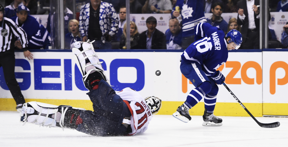 Washington goalie Braden Holtby dives at the puck in front of Toronto's Mitch Marner during the second period of a 4-3 overtime win by the Maple Leafs Monday at Toronto.