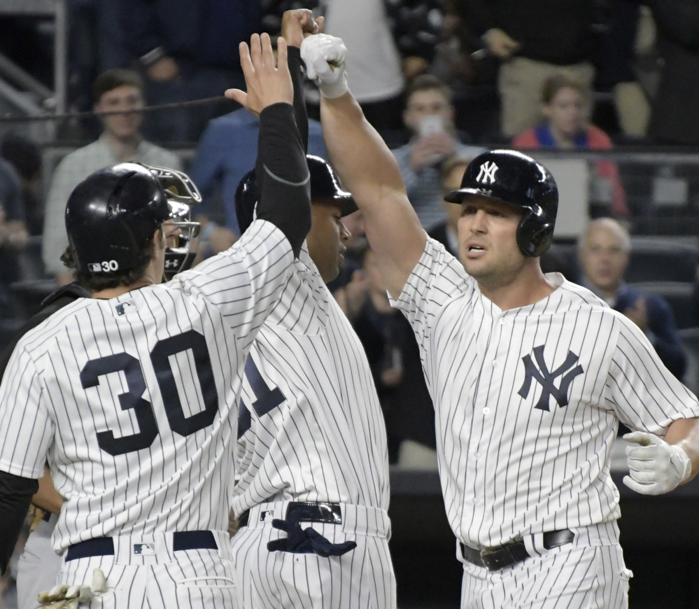 New York's Matt Holliday, right, celebrates with Aaron Hicks, center, and Pete Kozma after Holliday hit a three-run home run in the third inning of a 7-4 win by the Yankees at New York on Monday.