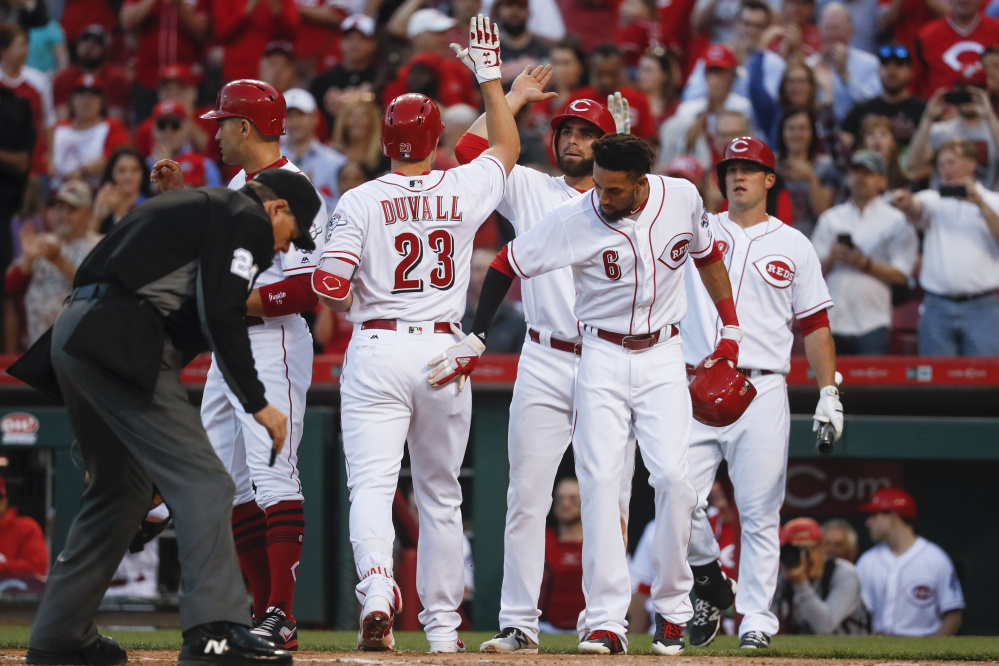 Adam Duvall of the Cincinnati Reds celebrates with his teammates Tuesday night after hitting a second-inning grand slam. The Reds defeated the Baltimore Orioles, 9-3.