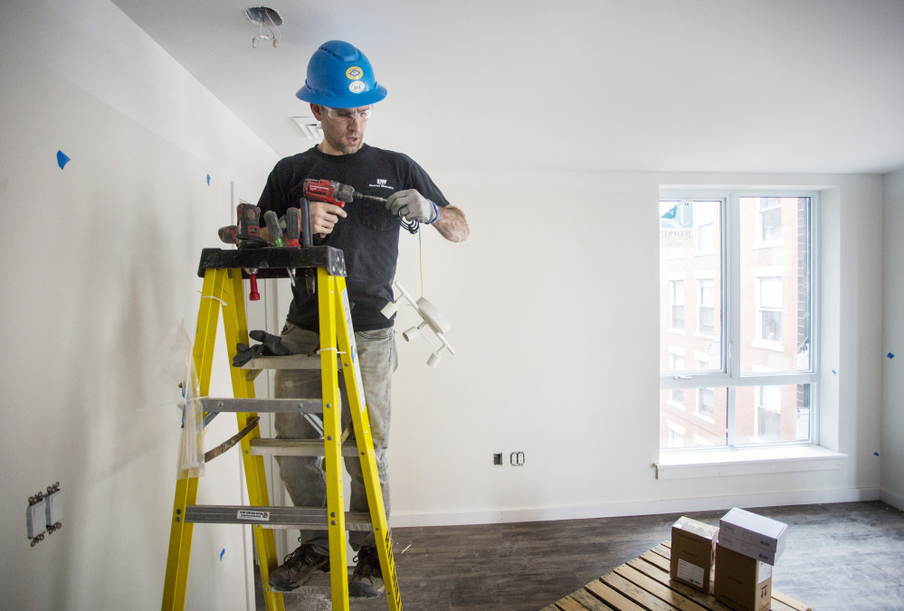 Seth Thompson, an electrician at B.H. Milliken, hangs lighting fixtures in an apartment at the Hiawatha building in Portland on Friday.