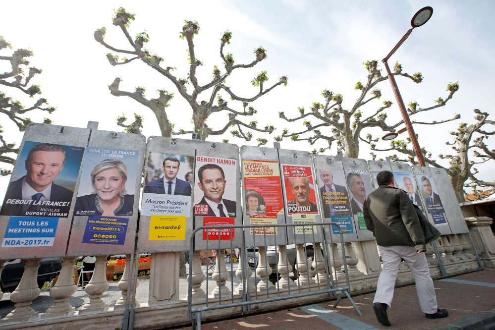 A man walks past campaign posters of the 11 candidates in Sunday's French presidential election, in Le Soler, France. The shadow over the EU's future comes in the form of not one but two candidates – far-right nationalist Marine Le Pen, second from left, and left-wing populist Jean-Luc Melenchon, third from right. Standing in the way of an EU meltdown: centrist Emmanuel Macron, third from left.