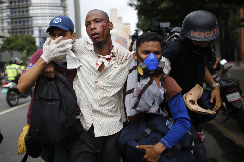 Paramedics assist a man injured during clashes with security forces during protests asking for the resignation of President Nicolas Maduro in Caracas, Venezuela, on Thursday. Tens of thousands of protesters flooded the streets in the biggest anti-government demonstrations in years.