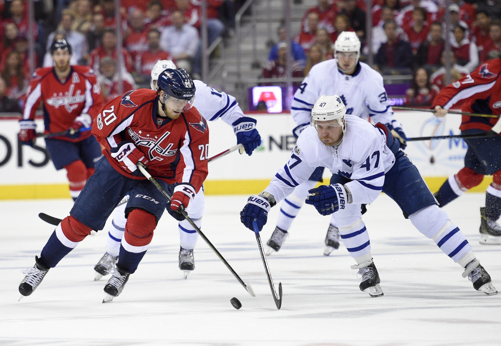 Washington's Lars Eller, left, battles for the puck with Toronto's Leo Komarov. The Capitals grabbed a 3-2 series lead with a 2-1 overtime victory and can advance to the second round with a win Sunday in Toronto.