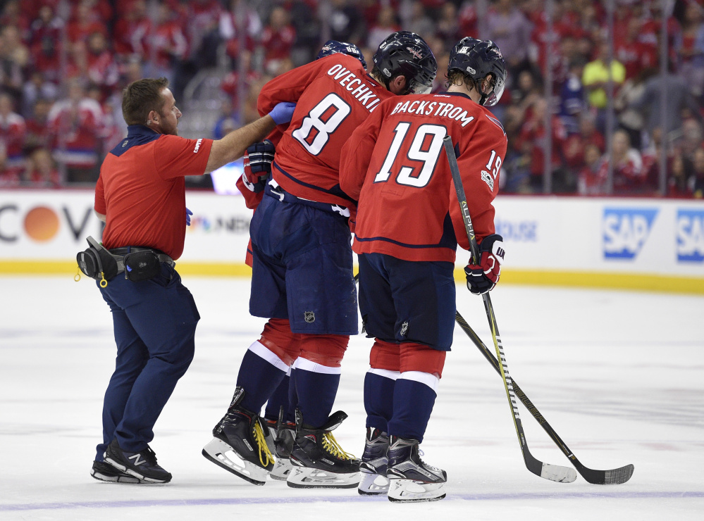 Capitals star Alexander Ovechkin is helped off the ice after he was injured in the first period Friday. Ovechkin missed the rest of the first period but returned in the second period.