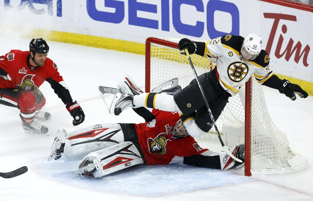 Boston's Sean Kuraly flies over Ottawa goalie Craig Anderson as Senators defenseman Marc Methot watches in the first overtime of Game 5 Friday in Ottawa, Ontario.