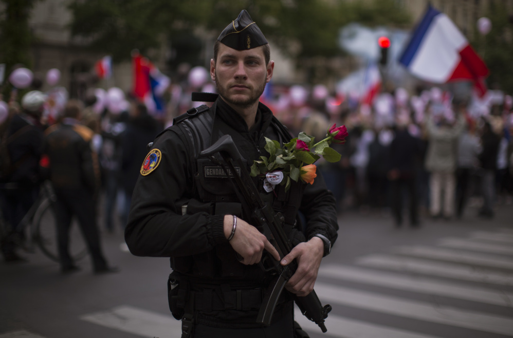 A French riot police officer carries flowers given to him by a protester who demonstrated with others in what was described as a march of support for all French security forces.