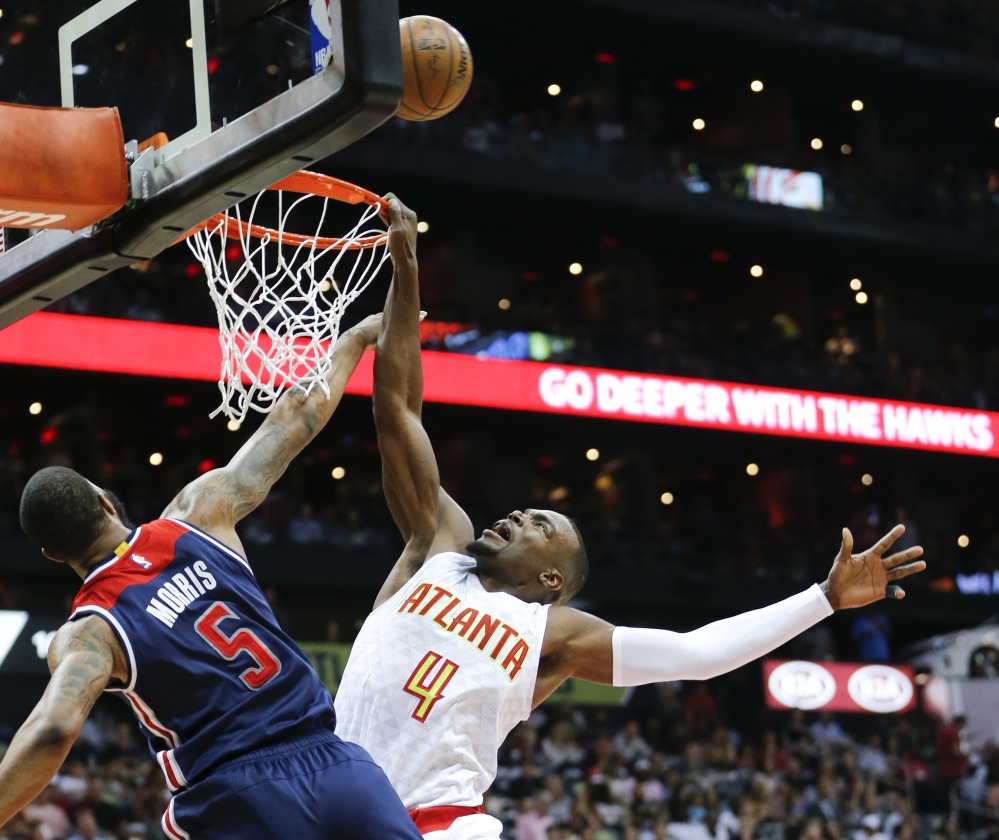 Atlanta forward Paul Millsap is fouled by Washington forward Markieff Morris during the first half of Game 3 of their first-round playoff series Saturday in Atlanta. The Hawks won 116-98 to cut the Wizards' lead to 2-1.