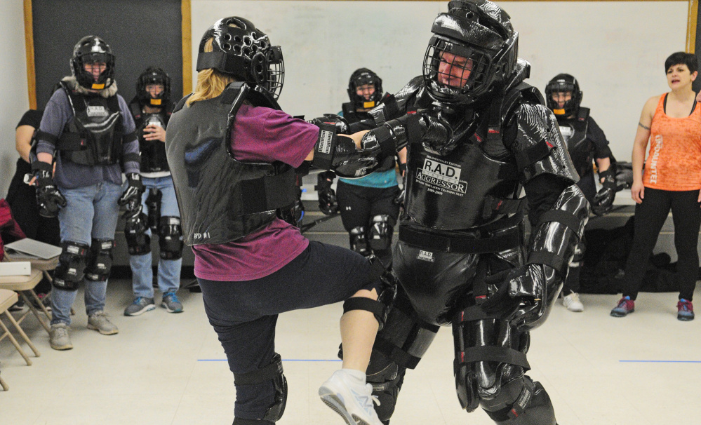 Ann Benson, 64, kicks a law enforcement officer playing an aggressor during a self-defense class.