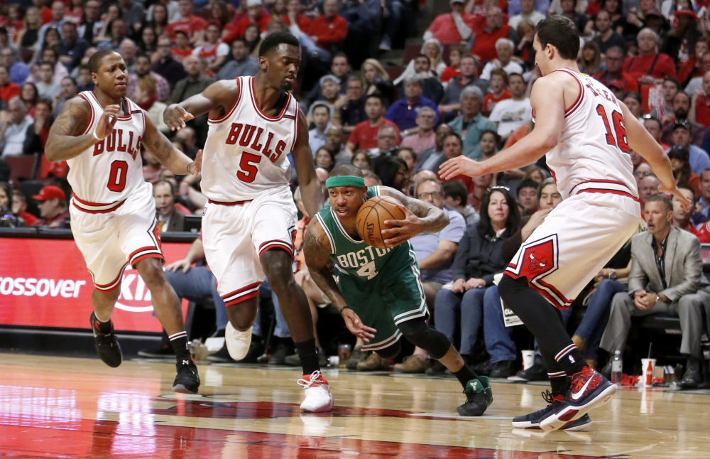 Boston's Isaiah Thomas dribbles through the Chicago defense of Isaiah Canaan, left, Bobby Portis, 5, and Paul Zipser during the first half of the Celtics' 104-95 win Sunday in Game 4 of their first-round series in Chicago. The series is tied 2-2.