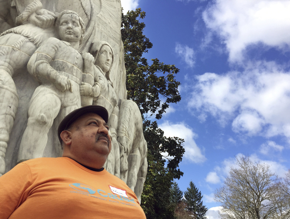 Moses Maldonado stands in front of a statue of pioneers at the Oregon Capitol in Salem, Ore. Maldonado attended a rally honoring farmworker organizer Cesar Chavez. in March.