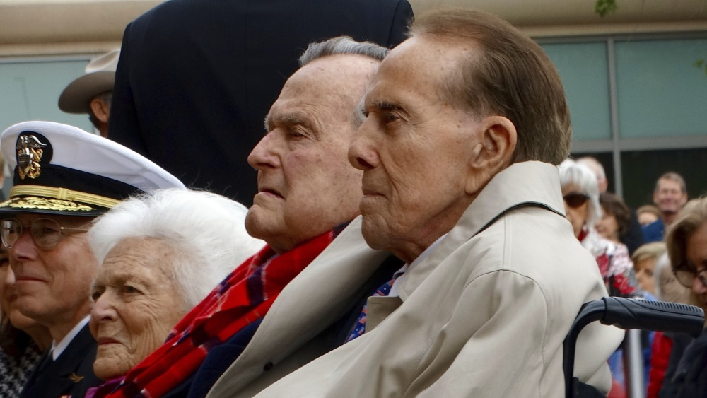Former Sen. Bob Dole, right, former President George H.W. Bush and former First Lady Barbara but sit together at a Pearl Harbor commemoration ceremony at the Bush Library Center in College Station, Texas, in December. A spokesman for former President Bush said Monday that the nation's 41st president will remain in a Houston hospital for a few more days of observation while he recovers from a mild case of pneumonia.