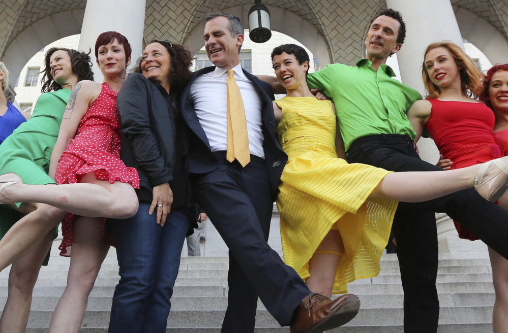 "Los Angeles Mayor Eric Garcetti, center, dances with the Bandaloop aerial dance troupe following its performance to a medley of songs from the movie ""La La Land"" on Tuesday."