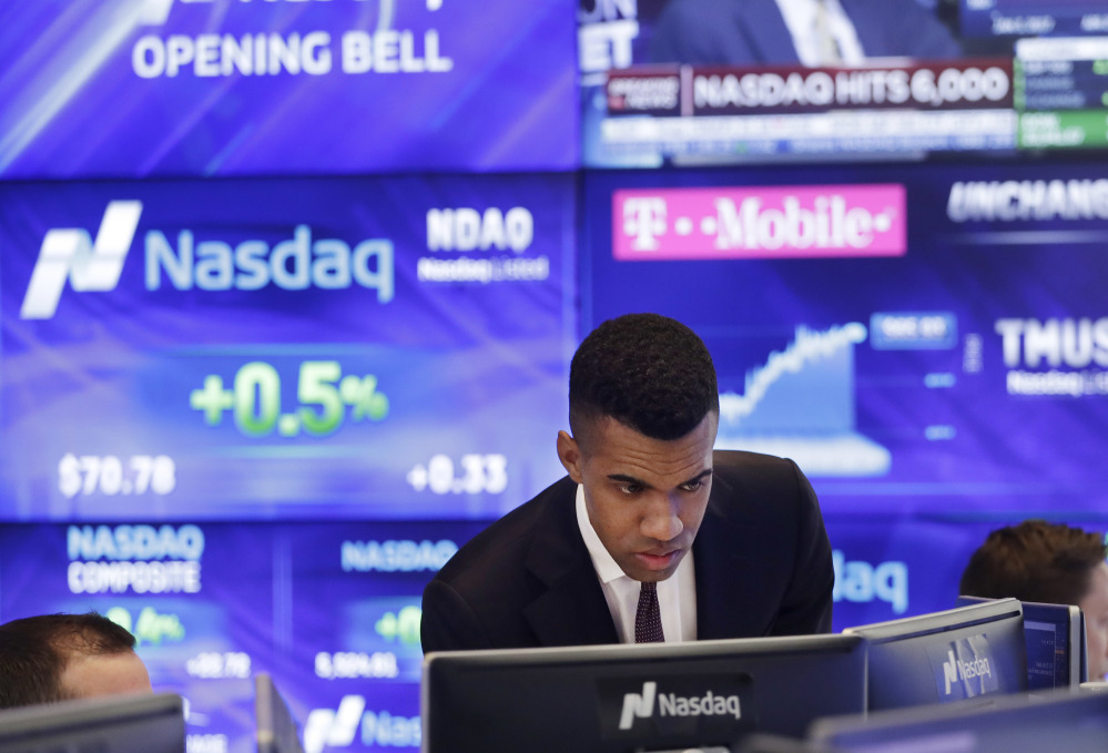 Brad Smith monitors stock prices at the Nasdaq MarketSite on Tuesday in New York. The Nasdaq Composite rose above 6,000 Tuesday, a record high.