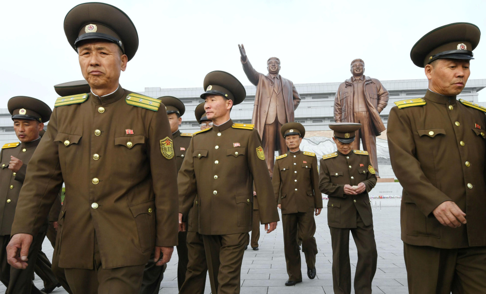 North Korean soldiers walk in front of bronze statues of North Korea's late founder Kim Il-sung and late leader Kim Jong Il at Mansudae in Pyongyang, in this photo released by Kyodo on Tuesday to mark the 85th anniversary of the founding of the Korean People's Army.