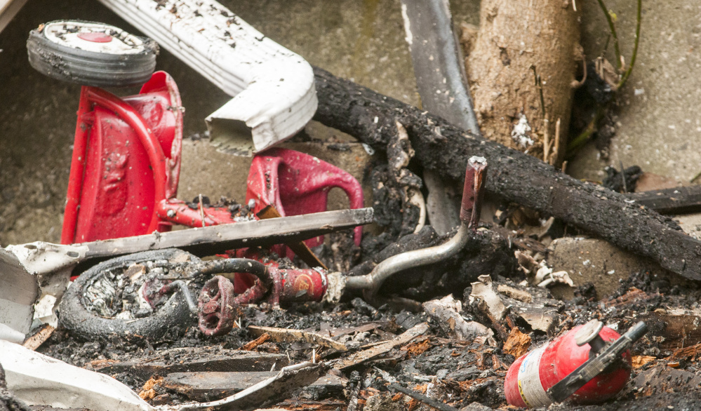 A tricycle and a fire extinguisher are among the detritus Tuesday in front of 94 Mount Vernon Ave. in Augusta. The building is expected to be demolished this week.