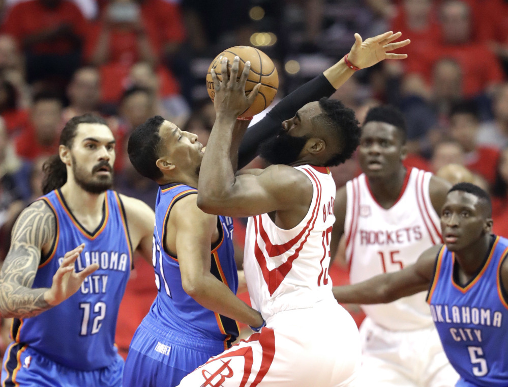 Houston's James Harden gets smacked by Oklahoma City's Andre Roberson as he drives toward the basket in Tuesday's game at Houston.