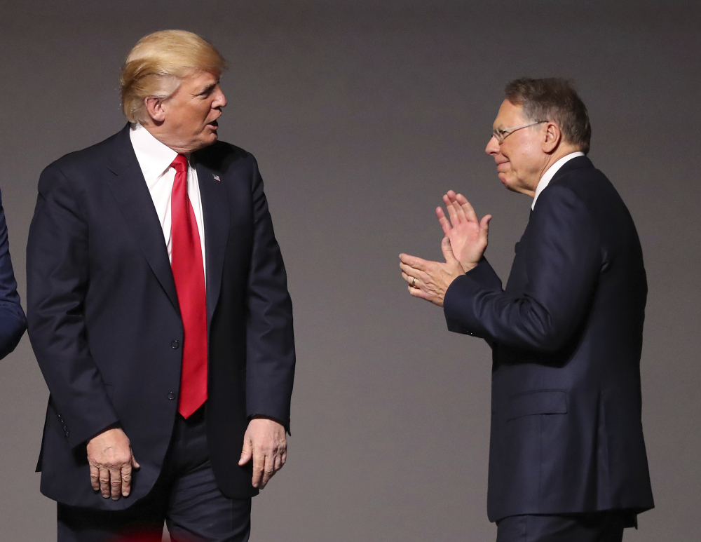 President Donald Trump, left, stands with National Rifle Association Executive Vice President Wayne LaPierre, right, as he arrives for the National Rifle Association Leadership Forum, Friday, April 28, 2017, in Atlanta. (Curtis Compton/Atlanta Journal-Constitution via AP)