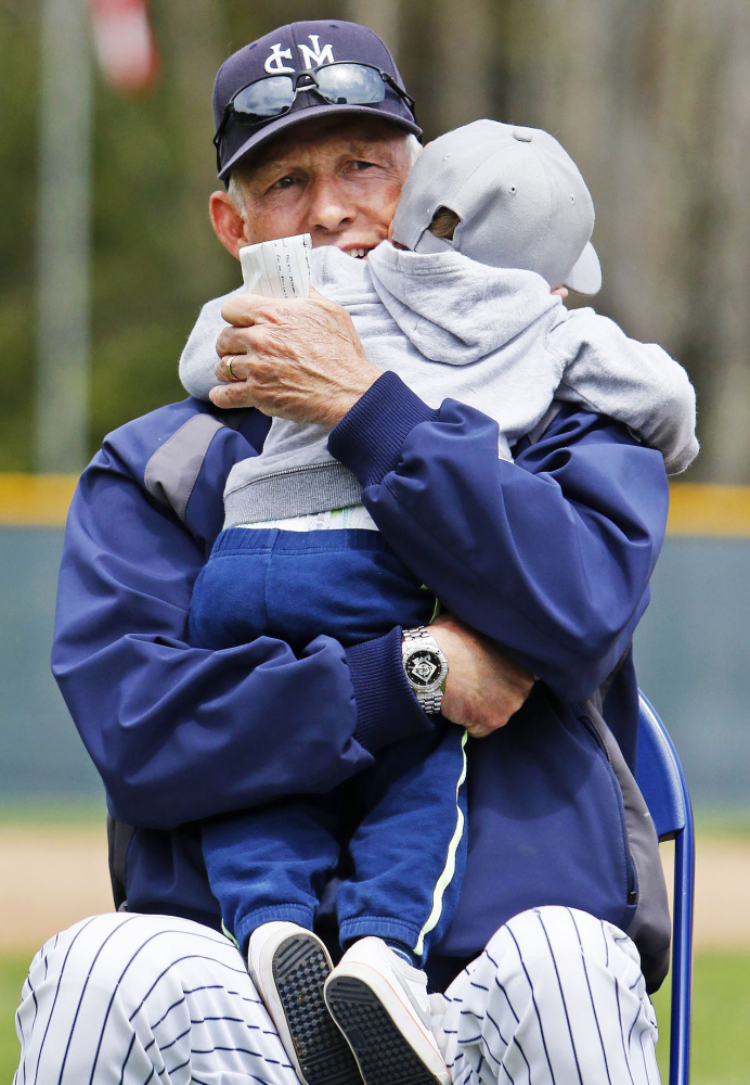 Ed Flaherty shares a hug with his grandson Kaden Booth while waiting for his turn to speak at Sunday's field dedication ceremony.