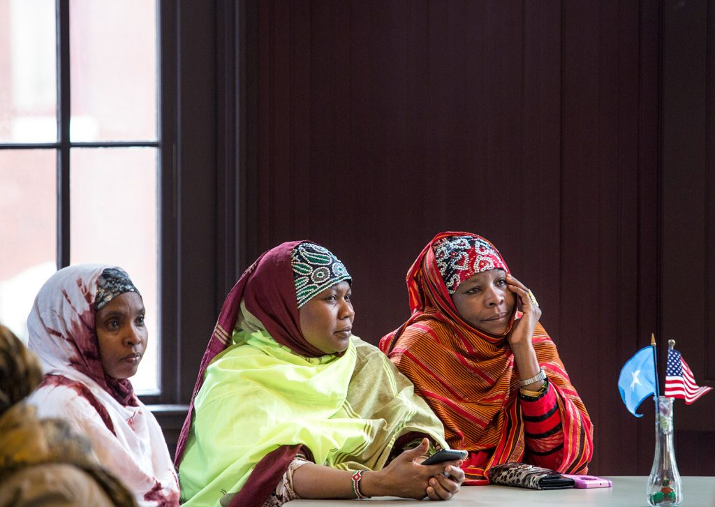 Lewiston residents Halima Mohamed, left, Khadijo Ibrahim and Jowhar Kabir, right, listen to Stephen Schwartz, U.S. ambassador to Somalia, at his public meeting in Lewiston on Thursday.