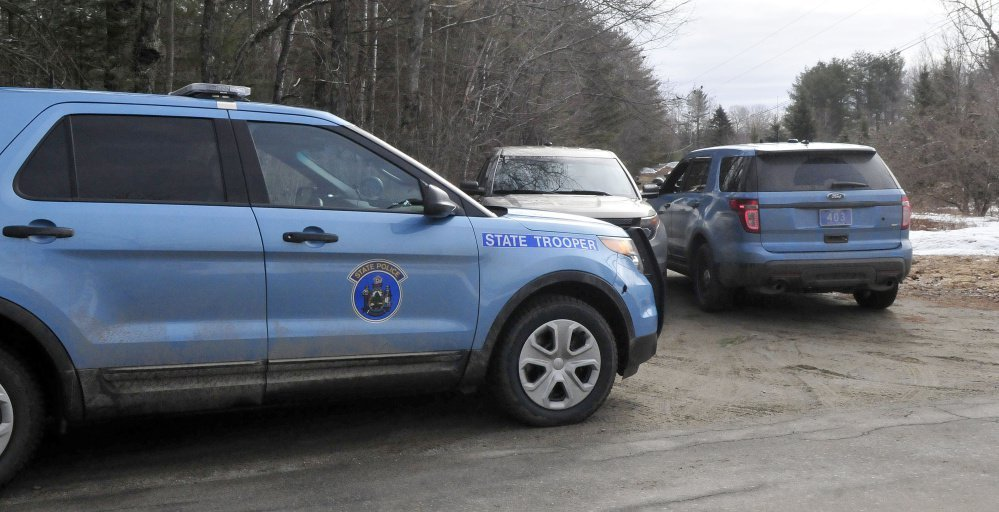 Maine State Police cruisers are parked at the end of a driveway on South Horseback Road in Burnham.
