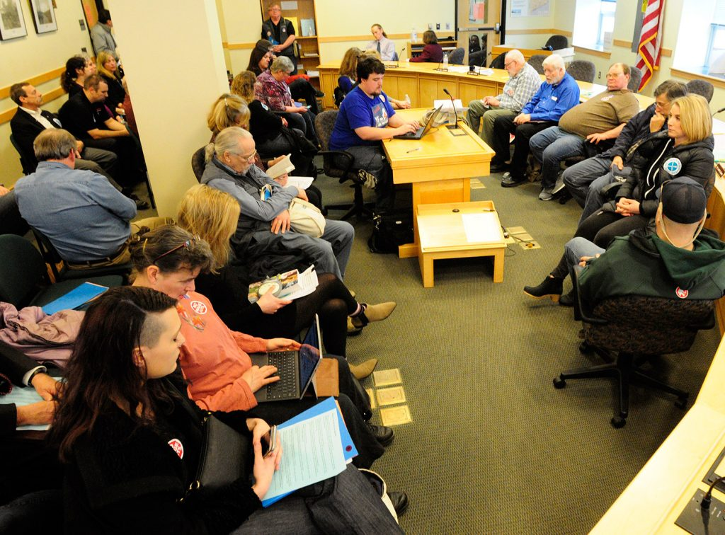 People sit in a nearby room waiting to testify Wednesday before the Labor, Commerce, Research and Economic Development Committee on two tip credit bills.