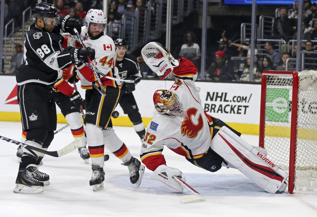 Calgary Flames goalie Jon Gillies of South Portland stretches to protect the goal, with defenseman Matt Bartkowski and Los Angeles Kings right winger Jarome Iginia in the mix during the second period Thursday night in Los Angeles.