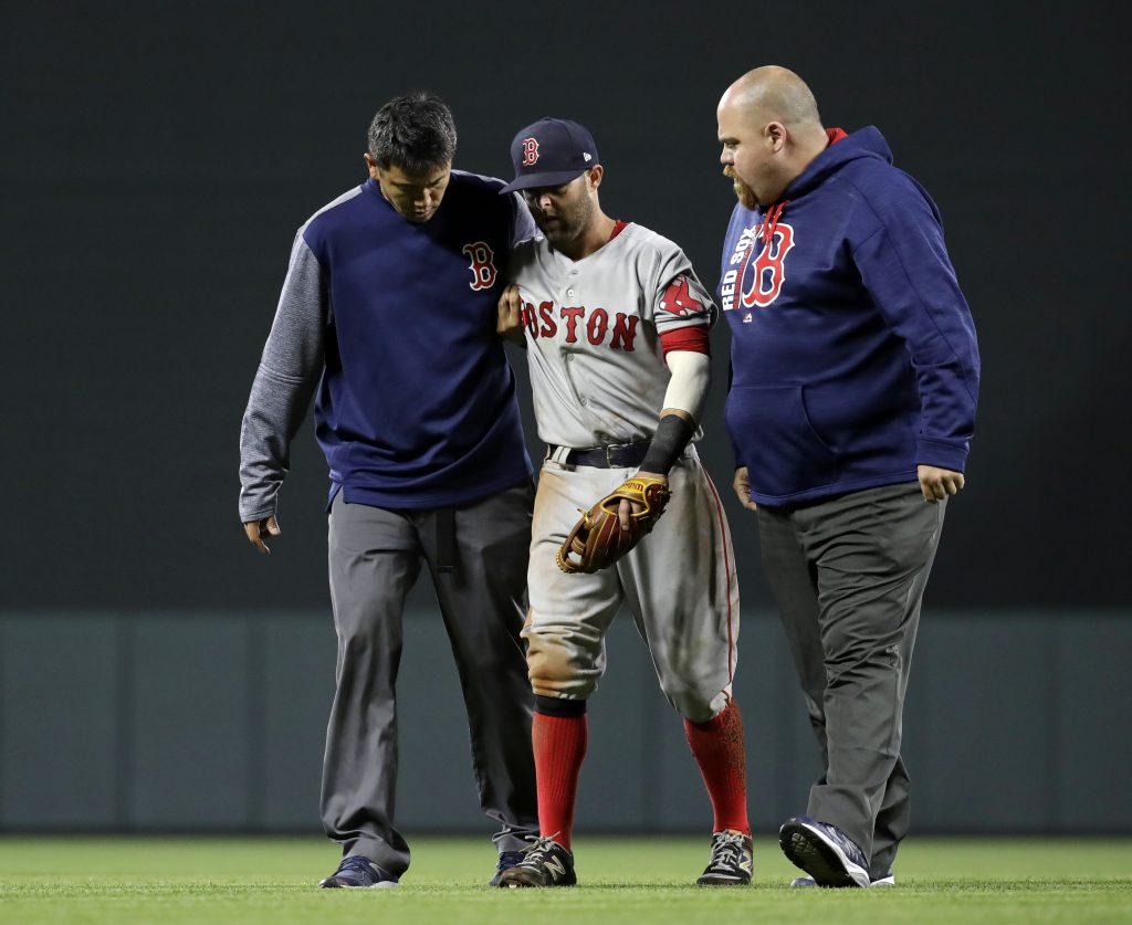 Red Sox second baseman Dustin Pedroia is assisted off the field after being injured during the eighth inning of Friday night's game in Baltimore.