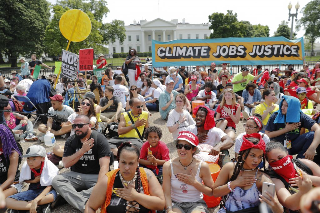 Demonstrators sit on the ground along Pennsylvania Avenue in front of the White House on Saturday during the People's Climate March.