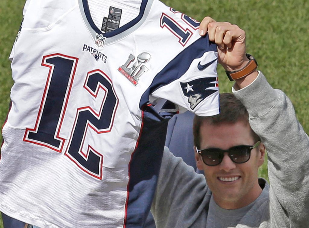 Tom Brady displays his recovered jersey during pregame ceremonies before the Red Sox opener at Fenway on Monday.