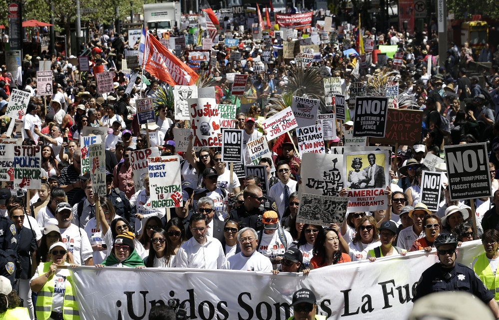 San Francisco Mayor Ed Lee, bottom center, walks with protesters on Market Street during a march in San Francisco on Monday. Immigrant groups and their allies joined forces to carry out marches, rallies and protests in cities nationwide to mark May Day.