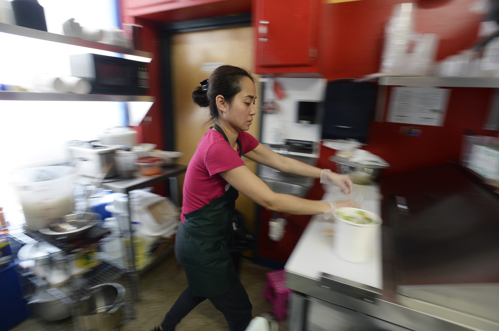 "Chau Du prepares an order at Pho Co. in the Public Market House on Thursday. She and her husband, Hoang Nguyen, opened their  food stand in December. Du, says her husband, is ""like an artist always working on a new masterpiece."""