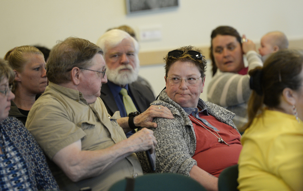 Gil Larrabee of Bangor comforts Donna Deigan of Brunswick after Deigan gave an emotional speech during Tuesday's hearing in Augusta on changes that have led many clients to lose mental health services.