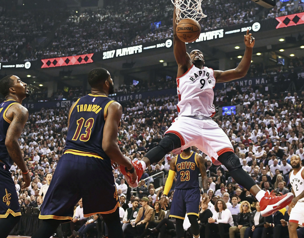 Toronto Raptors forward Serge Ibaka dunks as Cleveland Cavaliers guard JR Smith and center Tristan Thompson  look on during the first half of Game 3 of an NBA second-round playoff series in Toronto on Friday.